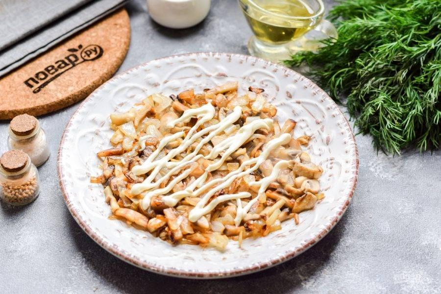 Выложите в салат первым слоем жареные грибы и лук, соль и перец добавьте по вкусу, смажьте майонезом.