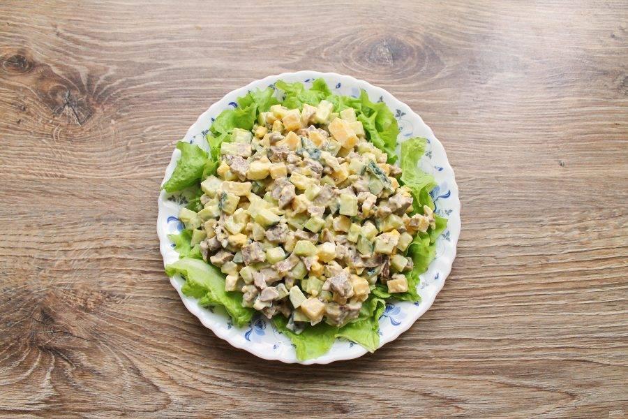 Переложите салат из миски на листья салата.