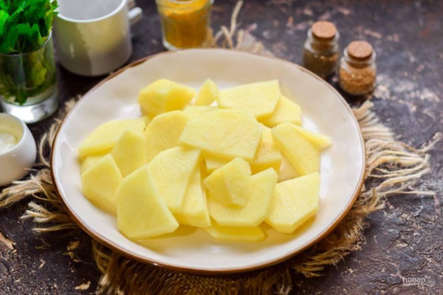 Картофель очистите, вымойте, просушите, нарежьте пластинами.