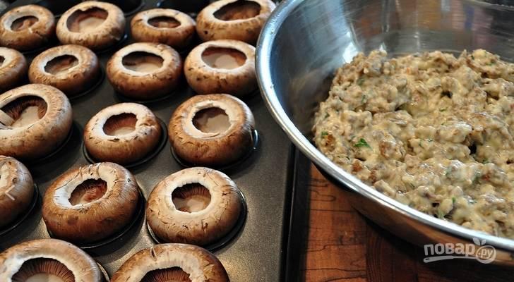 2. Смешаем для начинки тертый сыр, измельченный чеснок и колбаски, а затем добавим крем-сыр и специи, перемешаем и получим вот примерно такую смесь. Наполняем шапочки грибов этой смесью.