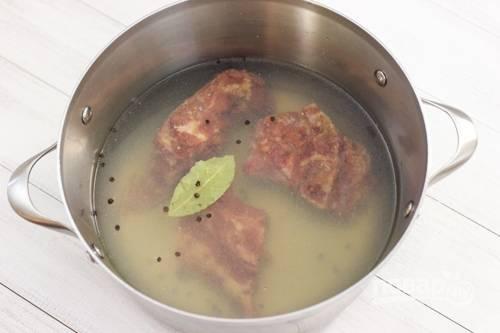1.Копченую свинину нарезаю кусочками, кладу в кастрюлю, добавляю лавровый лист и перец горошком, заливаю бульоном и водой. Отправляю кастрюлю на огонь.