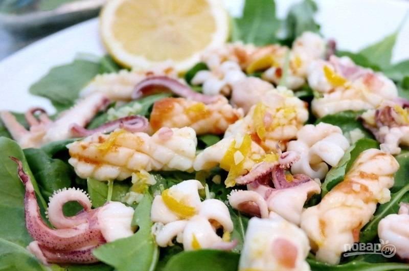 5.Вымойте рукколу, выложите её на плоскую тарелку, выложите кальмары. В другой миске смешайте оливковое масло, лимонный сок и цедру, полейте заправкой салат. Приятного аппетита!