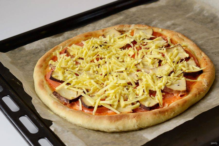 Натрите сыр на крупной терке, посыпьте им пиццу и отправьте в духовку еще на 10 минут.