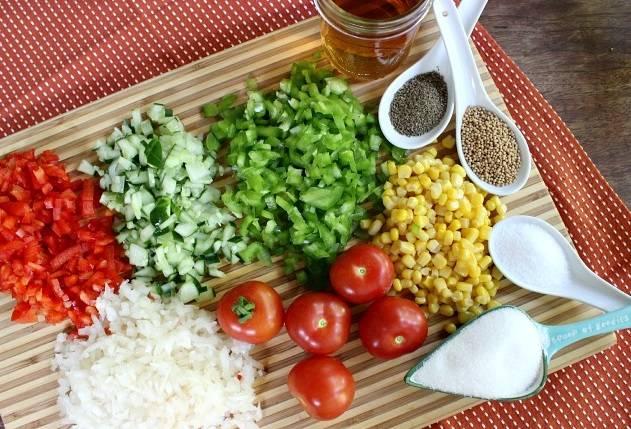 1. Итак, кукурузу отварите в небольшом количестве воды, если она у вас свежая. Можно срезать с початка и прокипятить в течение нескольких минут. Воду сохраните. Если используете консервированную, то жидкость не сливайте. Приготовьте все остальные ингредиенты. Очистите от кожуру (залив кипятком) помидоры, мелко нарежьте томаты, перец, огурцы и лук.
