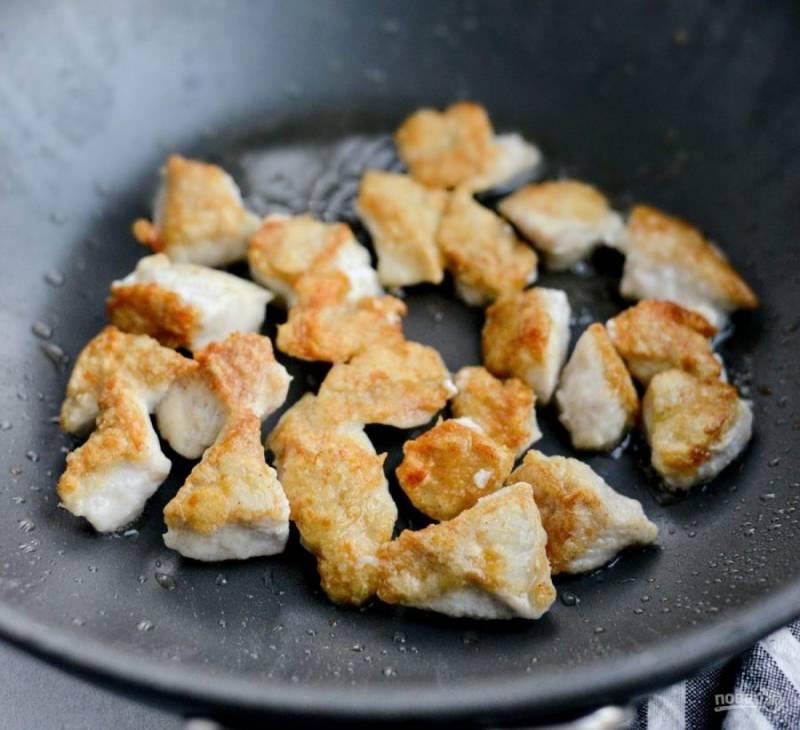 В специальной сковороде разогрейте масло. Обжарьте в нём порциями куриные кусочки до золотистой корочки, часто их переворачивая.