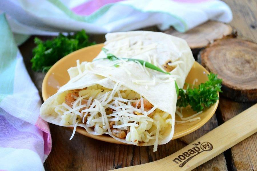 Круглый лист лаваша разрежьте пополам. На каждую половину положите макароны с креветками, заверните лаваш в виде конверта и закрепите зеленым луком. Сверху присыпьте натертым на мелкой терке твердым сыром.