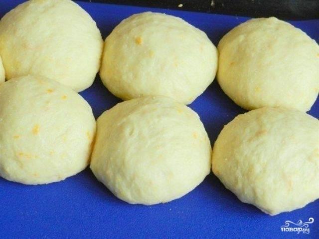 6. Выложите тесто на посыпанный мукой стол. Месите руками. Положите его в посуду. Накройте. Дайте возможность ему подняться. Для этого потребуется час. Затем достаньте увеличившееся в размере тесто и формируйте из него булочки.