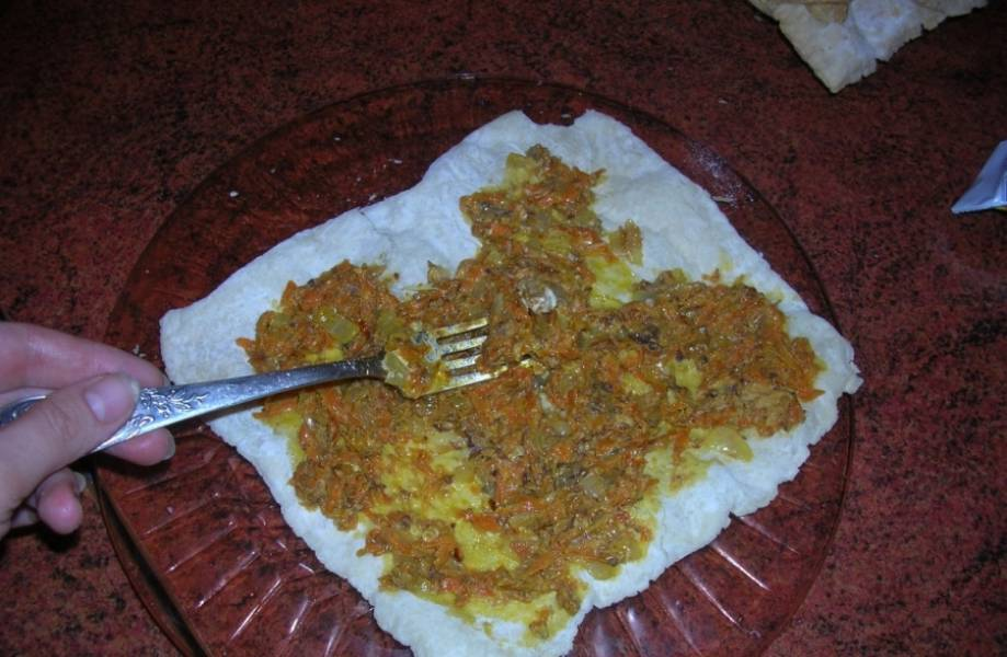 4. На блюдо кладем первый корж, промазываем его майонезом и выкладываем начинку. И так поступаем со всеми остальными коржами.