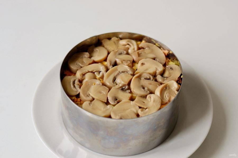 Готовый салат выложите в кольцо, украсьте грибами.