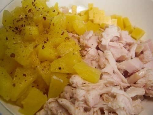 Для приготовления салата нам потребуется белое мясо копченой курицы. Это могут быть филе или грудка или же любое мясо с птицы, отделенное от кости и шкуры. Нарезаем его на небольшие кусочки или рвем пальцами на тонкие полоски. Тут уж как вашей душе угодно. Консервированные ананасы нужно достать из маринада и нарезать кубиками. В миске смешиваем куриное мясо с измельченными ананасами и добавляем щепотку мелко рубленного сухого перца Чили.