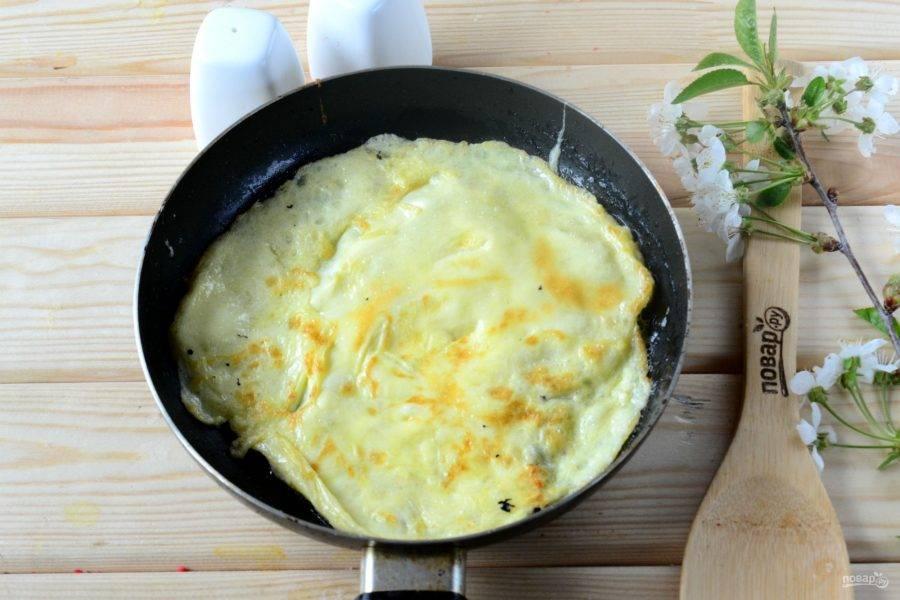 В сковороду, смазанную растительным маслом, налейте небольшое количество яичной смеси и быстро распределите смесь по всей плоскости сковороды, энергично вращая ею. Таким образом у нас получится красивый тонкий омлет, похожий на блинчик. Жарьте до румяного цвета. Переложите готовый омлет на тарелку и выпекайте омлетики из оставшейся яичной массы.