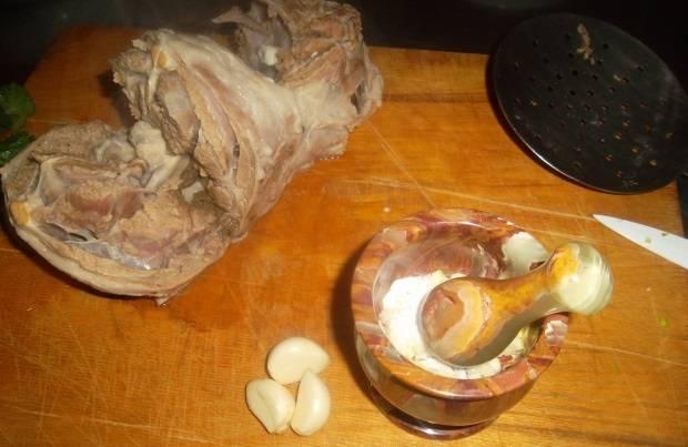 3. Через 3-4 часа мясо достанем из бульона. Режем его кусочками. В ступе начинаем перетирать чеснок и соль в расчета на каждого едока.