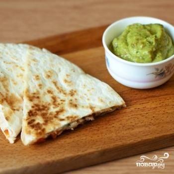 Каждую кесадилью разрезать на 3-4 части и подавать с заранее приготовленным соусом гуакамоле. Приятного аппетита!