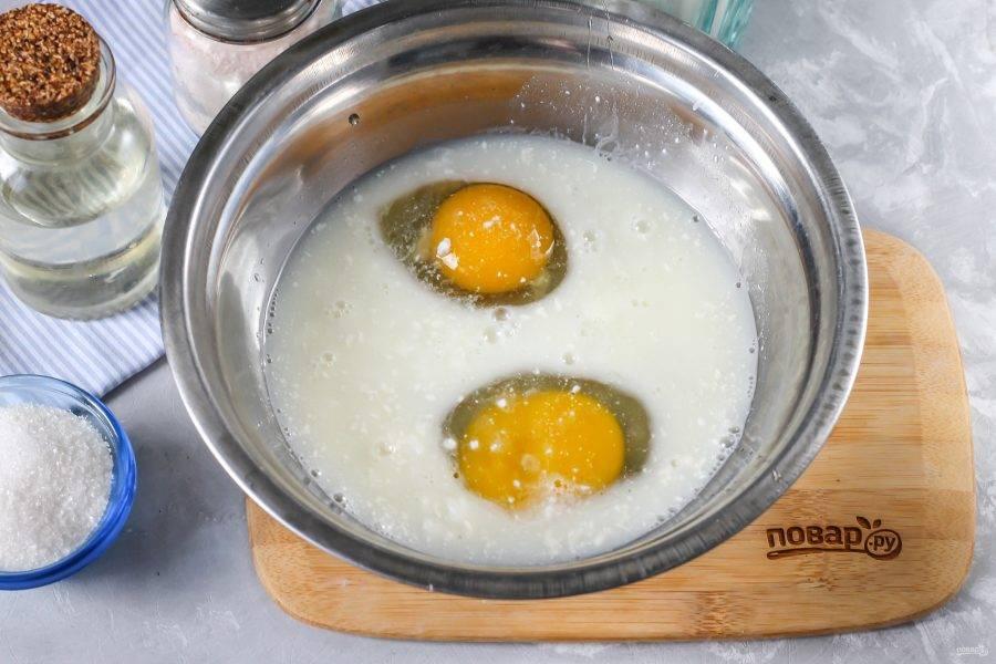 Вбейте куриные яйца в глубокую миску, влейте туда же простоквашу, всыпьте щепотку соли и сахар. Взбейте все венчиком или вилкой.