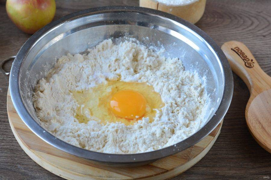 Разотрите муку с маслом чистыми руками, всыпьте соль, соду, вбейте куриное яйцо и влейте уксус. С уксусом тесто получится более слоеным.