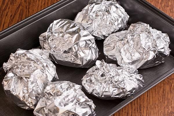 4. На дно жаропрочной формы выложите картофель, отправьте его в разогретую духовку. При средней температуре запекайте примерно 50-55 минут. Готовность можно проверить, аккуратно проколов картошку спичкой или зубочисткой.