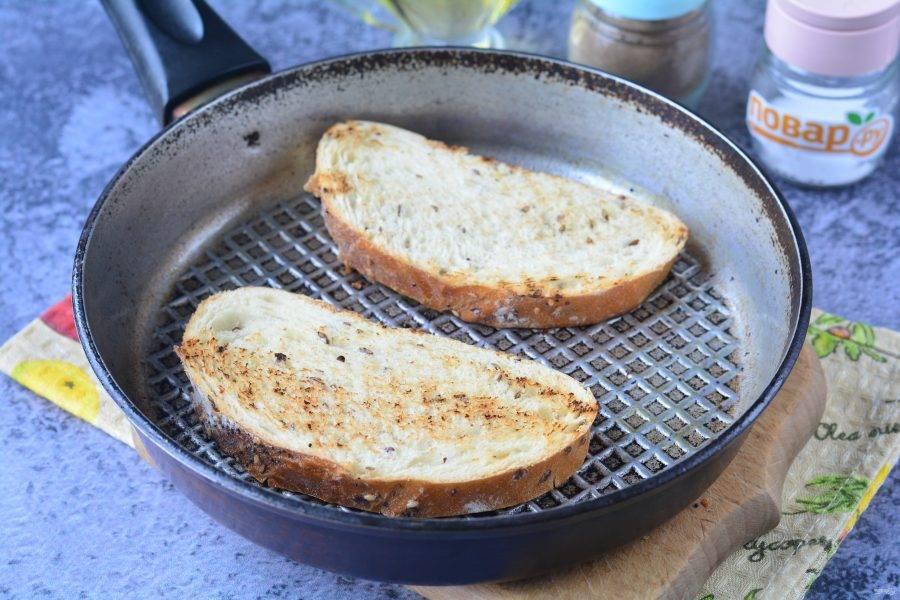 Обжарьте ломтики батона на сухой сковороде до появления румяной корочки.