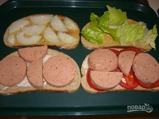 Ломтики хлеба подсушите на сухой сковороде или в тостере. На хлеб намажьте майонез, разложите отдельно листья салата, ломтики помидора, полукольца лука и ливерную колбасу.