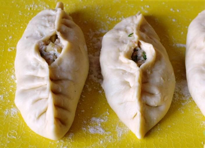 Соберите тесто вокруг начинки, защипните края теста, оставив посередине отверстие. В него налейте чайную ложку куриного бульона. Смажьте расстегаи желтком и отправьте в разогретую до 200 градусов духовку на полчаса. Готовые пироги выложите на полотенце, дайте им немного остыть, затем подайте на стол.