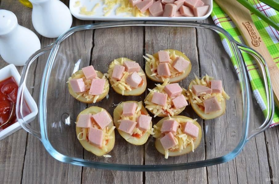 Сверху распределите кусочки колбасы или сосиски, порезанные колечками. Отправьте в духовку картофельные лодочки на 5 минут, температура — 200 градусов.