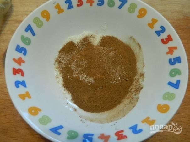 В небольшой посуде смешиваем 1/2 столовой ложки сахара и 1 чайную ложку корицы.