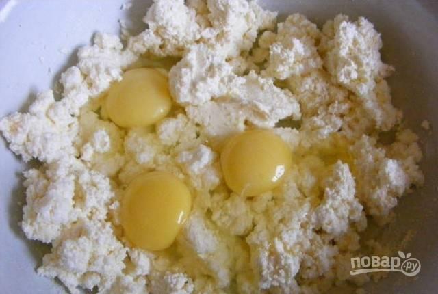 Вбейте в творог яйца. Добавьте соль и соду.