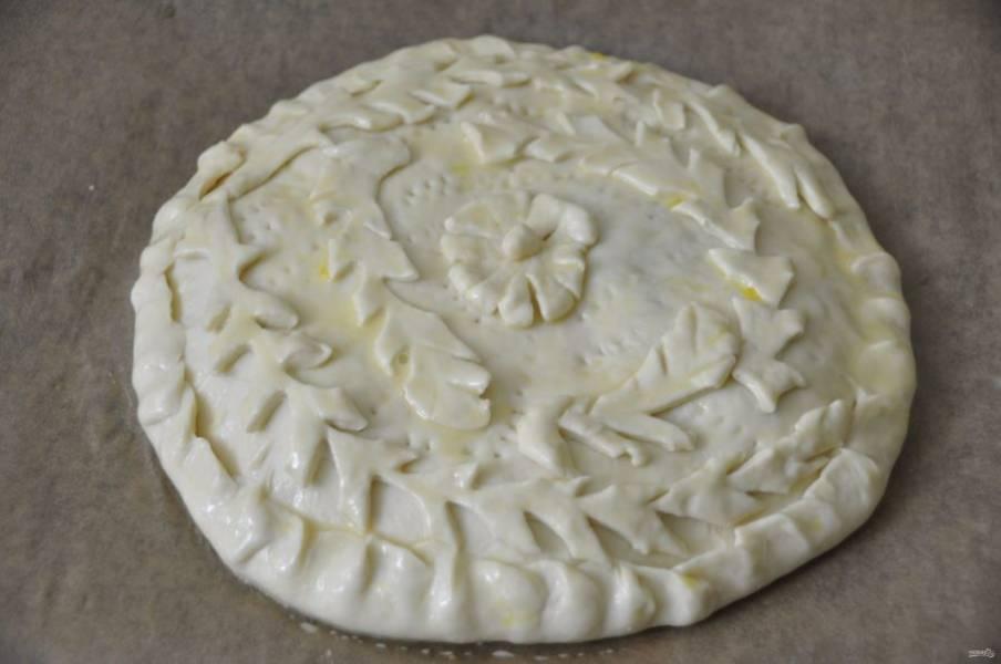 Накройте пластом теста, хорошо защипните края. Из маленького кусочка теста вырежьте украшения, это не обязательно, но с ними пирог получается нарядным. Смажьте смесью яйца с молоком или просто молоком, сделайте вилкой проколы.