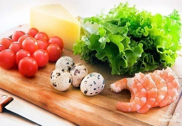 Вымойте листы салата  и черри под струей холодной воды. Оботрите их сухим полотенцем. Сварите в соленой воде яйца и креветки до готовности.