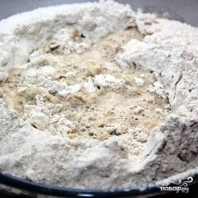 Просеиваем в миску муку (ржаную и пшеничную), дрожжи и соль. Вливаем в смесь 325 мл теплой воды.