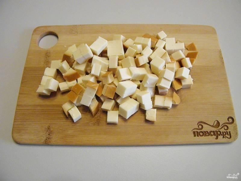 Колбасный сыр освободите от пленки, порежьте кубиками.