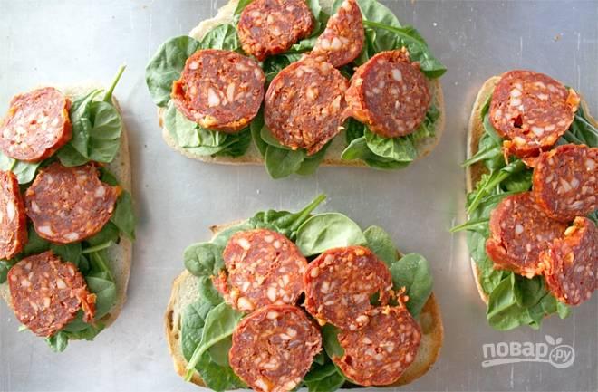 1.Нарежьте хлеб ломтиками, каждый поджарьте на сухой сковороде или на гриле. Нарежьте кусочками колбаску, вымойте шпинат. На кусочек хлеба уложите несколько листов шпината и колбасы.