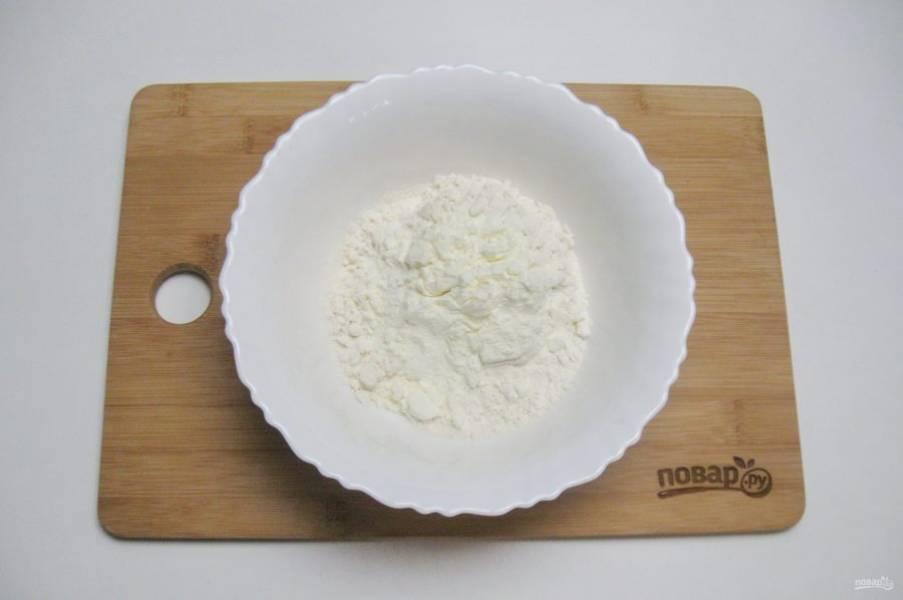 Половину нормы муки просейте в глубокую миску. Добавьте сухое молоко.