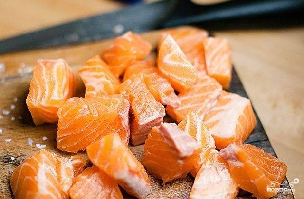 Филе форели нарежьте на кубики. Обжаривайте их 3 минуты в двух ложках оливкового масла на сковороде. Также влейте кунжутное масло, посолите.