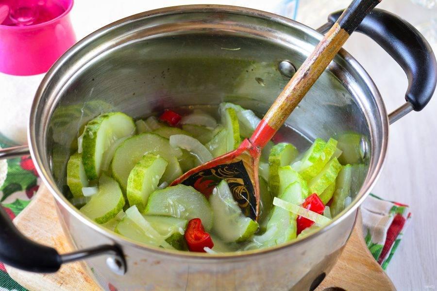 Тушите салат 20-25 минут на среднем огне, пока огурцы не станут более мягкими. В процессе приготовления огурцы уменьшатся в объеме, а маринада - жидкости станет больше.