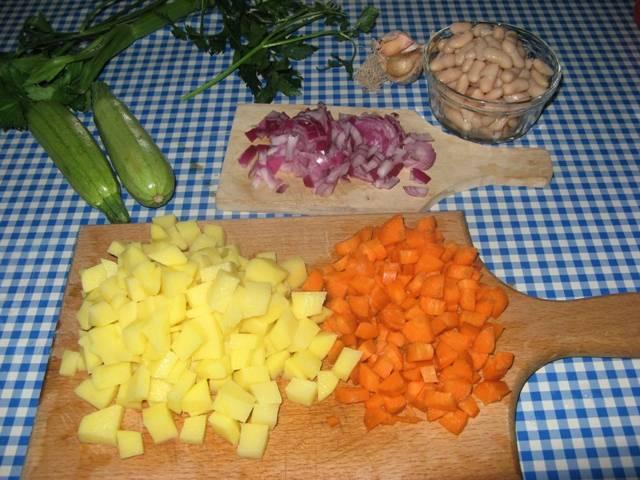 Теперь быстренько чистим овощи и нарезаем их. Картофель и морковь режем небольшими кубиками, лук измельчаем, а с фасоли сливаем воду и промываем ее.