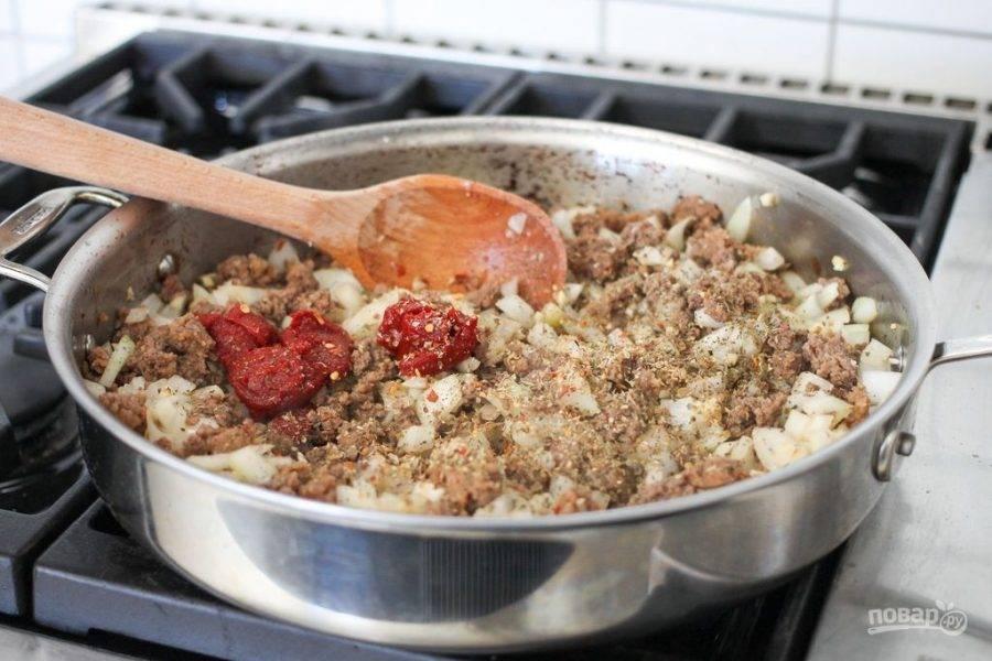 Как только мясо станет коричневатого оттенка, добавьте в него лук с чесноком, томатную пасту и итальянские травы.