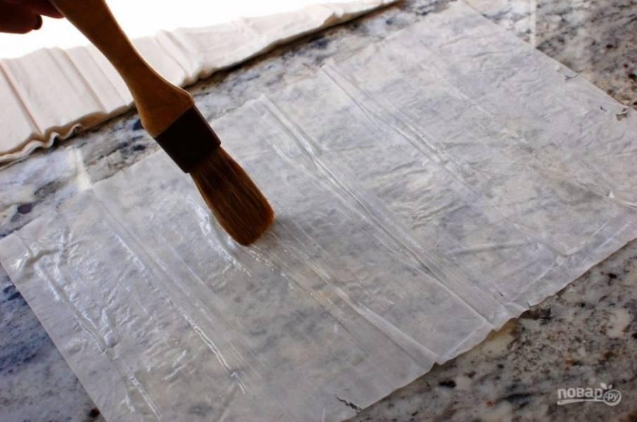1.За ночь до приготовления разморозьте тесто в холодильнике. Разделите тесто на листы. Растопите сливочное масло и смажьте один лист.