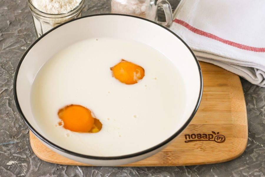 Вбейте куриные яйца в глубокую емкость. Влейте молоко любой жирности и добавьте сахар, соль. Взбейте все венчиком примерно 1-2 минуты.