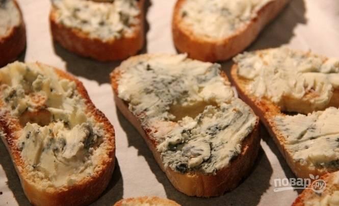 На кусочки батона намажьте сыр. Отправьте их в духовку на 6 минут при 180 градусах.