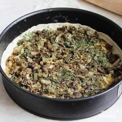 Обжаренные грибы с луком выкладываем поверх слегка запекшегося теста. Солим, перчим, добавляем любимые специи.