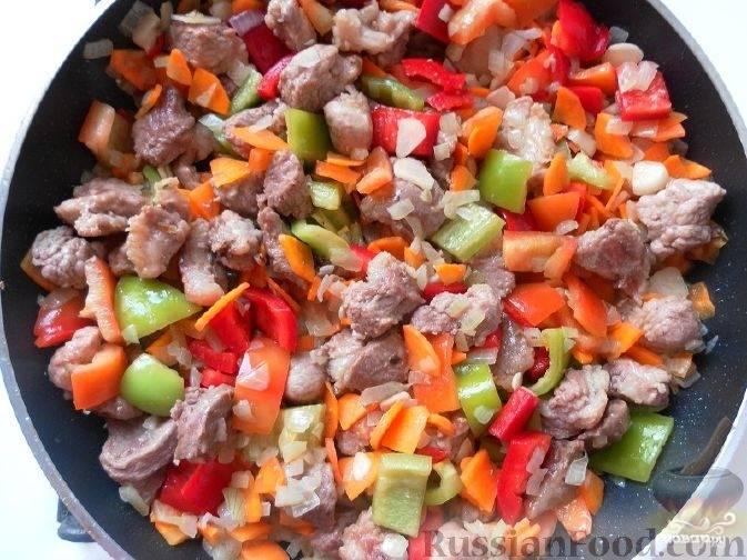4. Помойте и очистите от плодоножки перцы. Освободите их от семян. Затем нарежьте кусочками. Очищенный чеснок нарежьте тонкими пластинами. При желании нарежьте стручок острого перца. Все виды перца и чеснок соедините с мясом. Перемешайте и подержите на огне не больше 30 секунд. Затем добавьте томатную пасту. Потушите под крышкой  не больше одной минуты на малом огне.