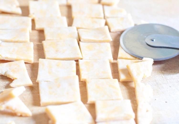 2.Разделите тесто на части, каждую раскатайте в пласт около 0,5 см в толщину и острым ножом разрежьте на маленькие квадратики.