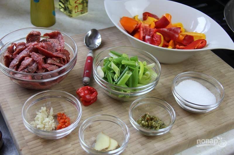 1. Очистите и измельчите сладкий перец, нарежьте зеленый лук, имбирь, чеснок. Вымойте, обсушите и тонкими полосками нарежьте мясо.