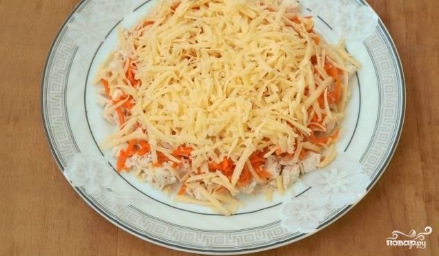 Далее выложите морковь. Сверху натрите сыр на крупной тёрке. Намажьте его майонезом.