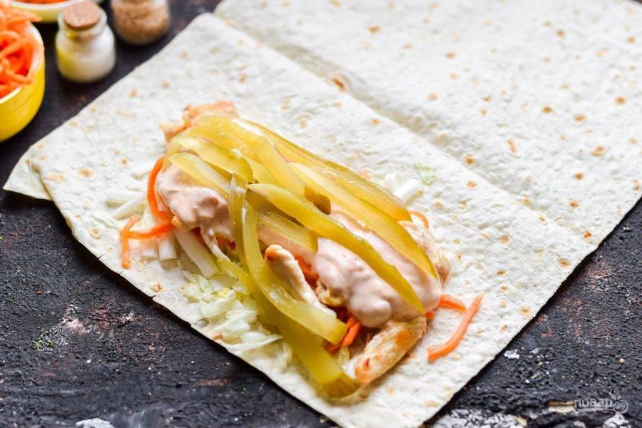 Полейте все остатками соуса и выложите нарезанный полосками соленый огурец.