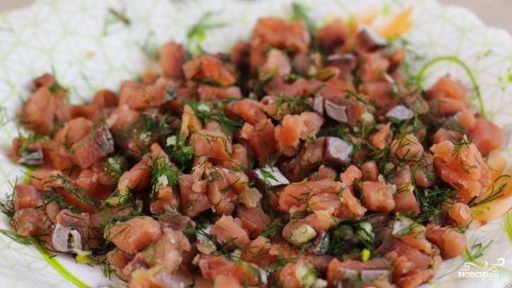 Рыбу очистите от чешуи и косточек. Нарежьте маленькими кусочками. Добавьте к ней пропущенный чеснок через чеснокодавку и измельчённый укроп. Перемешайте.
