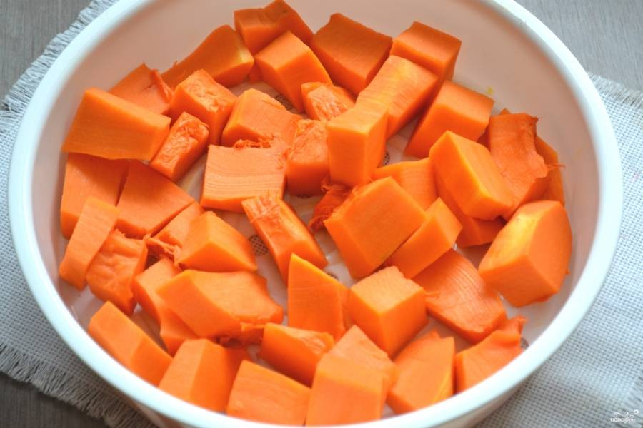 Чтобы тесто для оладий получилось очень нежным и однородним, тыкву необходимо отварить на пару до готовности. Порежьте мякоть тыквы кубиками и выложите в специальную форму для приготовления в мультварке на пару. Включите соответствующий режим в вашей мультиварке на 20 минут.