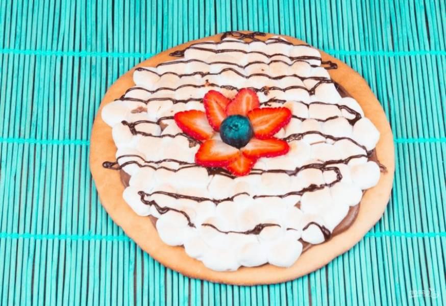 5. Пицца будет готова, когда маршмеллоу станет слегка золотистым. Полейте пиццу растопленным шоколадом и украсьте фруктами. Приятного аппетита!