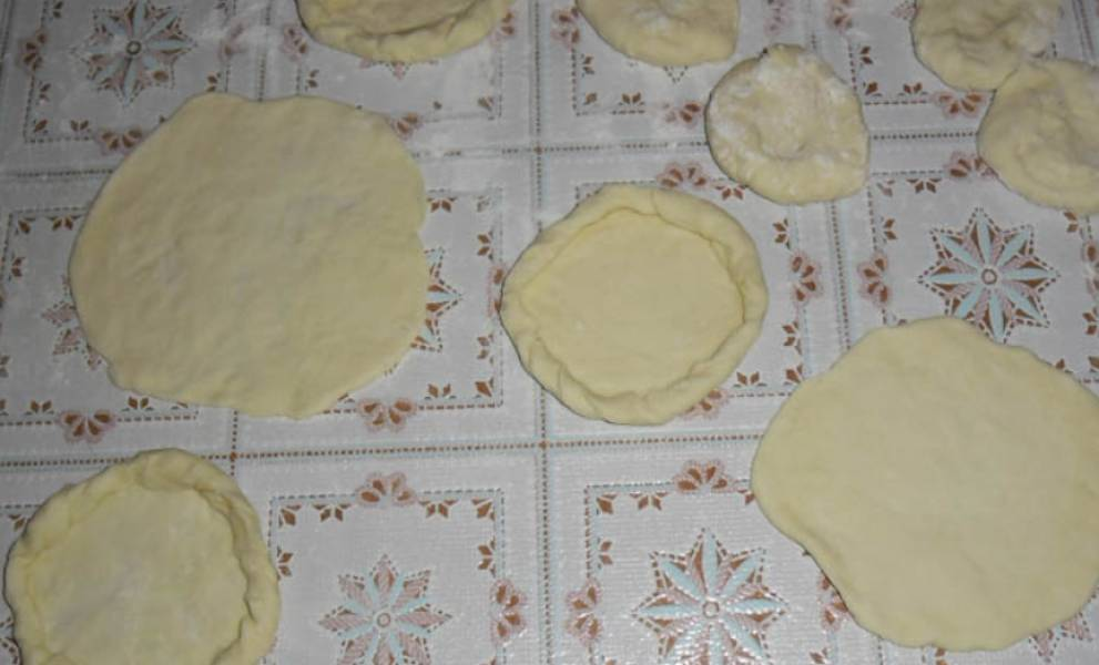 Разделите тесто на колбаски, каждую разрежьте на части и раскатайте в лепешки.