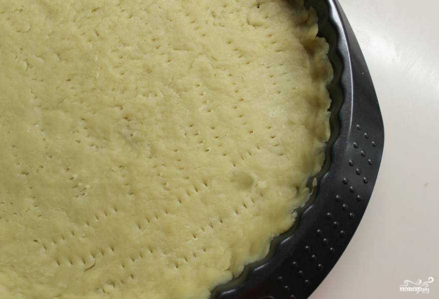 Тесто раскатываем и укладываем в широкую форму, сформируем высокие бортики. Делаем в тесте проколы вилкой. Ставим форму в холодильник на 30 минут.